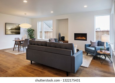 Interior living area with lots of seating with lights on facing the fire place