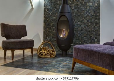 Interior of living room in modern style with elements of stone. Fireplace where burning fire and basket with firewood near. Two armchair and little table around.