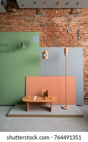 Interior in a loft style with brick wall and colorful furniture. There is a small metallic orange table with supports, candlestick and lamp hanging multicolored metal lamps and panels with hangers.