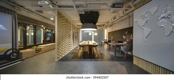 Interior in a loft style. There are tables and chairs. There are notebooks, laptops, holders with pens and grass decoration on the tables. Above them hang large lamps with artificial leaves. A few