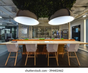 Interior in a loft style. Wooden table with stand for office supplies. There are grass decorations on the stand. Above the table hang large lamps with artificial leaves. There are notebooks on the