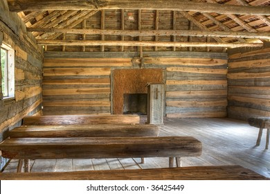 Interior of a log cabin vintage church in natural light with benches and pulpit.