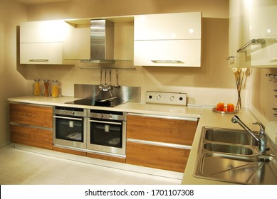 Interior of luxurious modern kitchen equipment, white and walnut cabinets