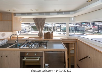 Interior of the luxury sailing catamaran - salon and cabin. Large and bright lounge with galley. Spacious cabin with high double bed and bright interior. Finishing with light wood VIP yachts