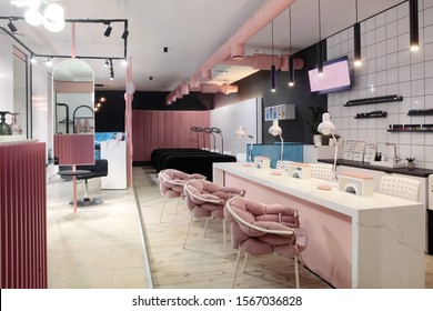 Interior of luxury stylish beauty salon.First plan pink armchairs and table for manicure and second plan place for eyelash extension .Pink concept design