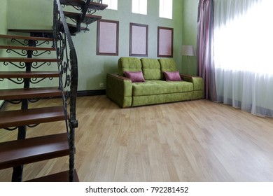 Interior with a metallic black staircase with wooden steps and a green sofa in the living room