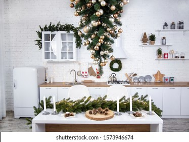 Interior of minimalistic kitchen with white walls, white floor, white countertops. Kitchen with white furniture. Kitchen decorated with  garlands and Christmas toys. Christmas tree upside down.