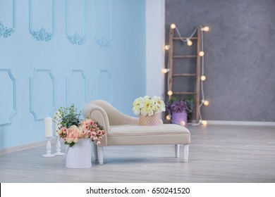 Interior mock up photo. Blue wall with leather material divan sofa and pot with plant flowers and ladder. Background photo with copy space for text