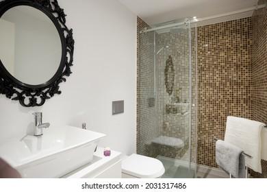 Die Inneneinrichtung eines modernen Badezimmers ist mit einem schwarzen Spiegel, braunen Fliesen und einer Duschkabine ausgestattet