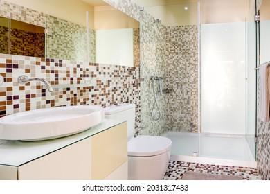 Interieur eines modernen Badezimmers mit braunen Fliesen und großer Duschkabine