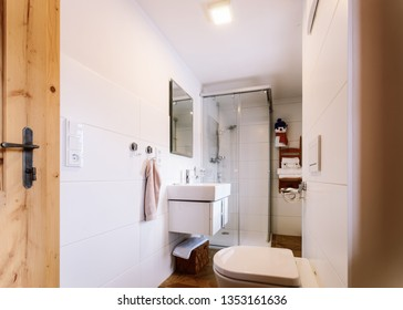 Interior of modern bathroom with wood design. Home with mirror, sink, toilet bowl and shower. Hotel bath room. House with toilet furniture and decor. Wall and floor on background. Wooden decoration.