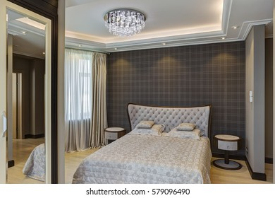Interior of modern bedroom in gray color and wall in checked print. Comfortable bed, wardrobe with mirror built into wall and crystal chandelier in center of ceiling. Lighting room with big windows.