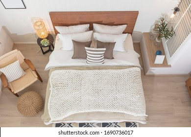 Interior of modern bedroom with white mattress, wooden floor, armchair and small wardrobe. Top view of spacious bedroom.