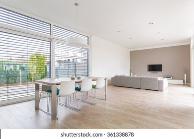 Interior of a modern bright dining-room with large windows