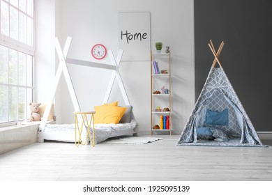 Interior of modern children's room with play tent and bed