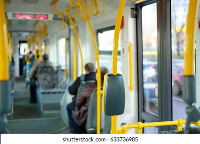 Interior of modern city articulated low floor tram with seats, yellow handles and passengers