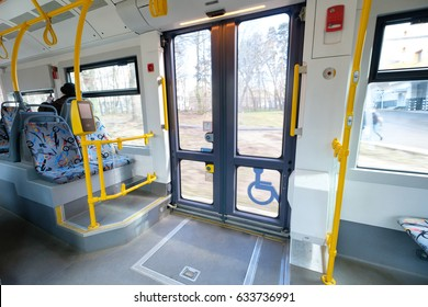 Interior of modern city articulated low floor tram with seats, yellow handles. Wide angle shot of front doors