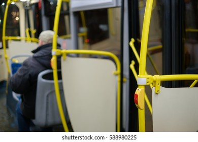 Interior of modern city bus with yellow handles with stop alert, seats and passengers in night