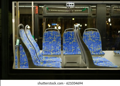 Interior of modern city low floor city tram with seats and hand grips in night