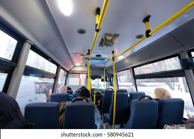 Interior of modern city mini bus wide angle shot with seats, passengers and hangers in winter day