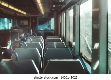 An interior of a modern empty ordinary suburban train in Europe with a row of double seats, shallow depth of field with selective focus, railroad tracks outside the window