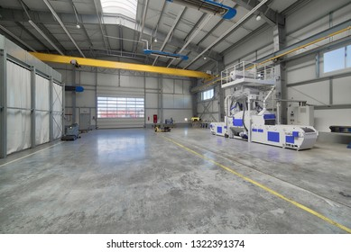 Interior of a modern factory. A bright large workshop, inside there is a shot blasting unit.