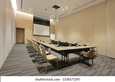 Interior of modern fully equipped professional facilities meeting conference room boardroom classroom office with nobody empty and  microphones white projector board chairs door business meeting venue
