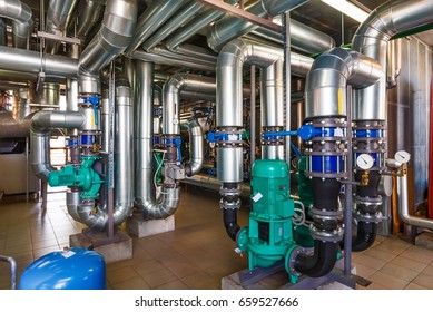 The interior of a modern gas boiler house with pumps, valves, a multitude of sensors and barrels.