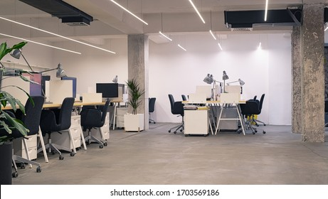 Interior of modern industrial office with desks and computers. Empty open space office with essential amenities. Stylish coworking area with furniture.