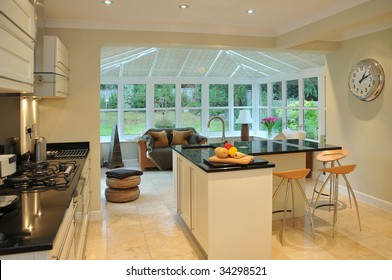 Interior of a modern kitchen with beyond a conservatory and garden