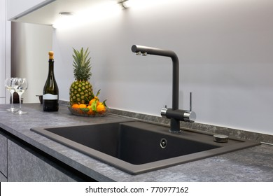The interior of the modern kitchen is illuminated with a gray stone countertop with a luxury washbasin and mixer faucet , fruit pineapple and tangerines, a bottle with red wine and two glasses.