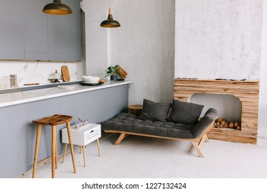 Interior of the modern loft kitchen-studio in the apartment. Room, furniture, sofa near wooden fireplace.