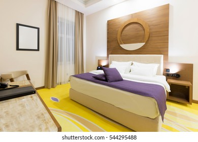 Interior of a modern new hotel double bed bedroom in the evening