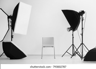 Interior of modern photo studio with chair and professional equipment