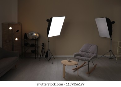 Interior of modern photo studio with rocking chair, table and professional equipment