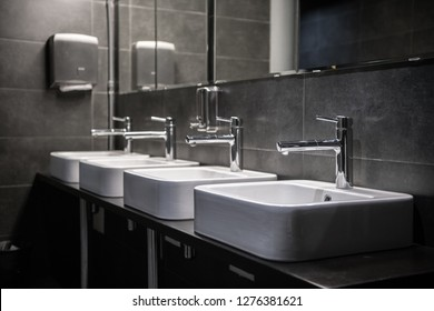 Interior of a modern public bathroom toilet in grey colors