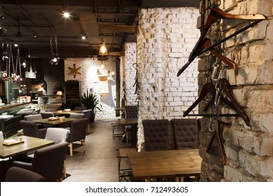 Interior of modern restaurant. Contemporary design in loft style, big cozy hall with tables and private cabins with brick wall, copy space