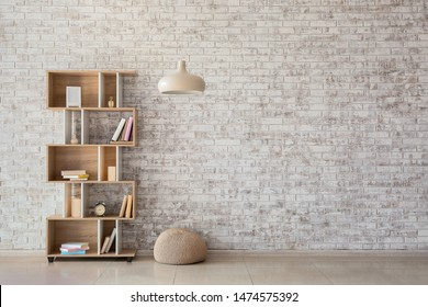 Interior of modern room with bookcase, pouf and lamp