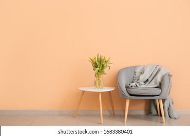 Interior of modern room with comfortable armchair and table with spring flowers near color wall