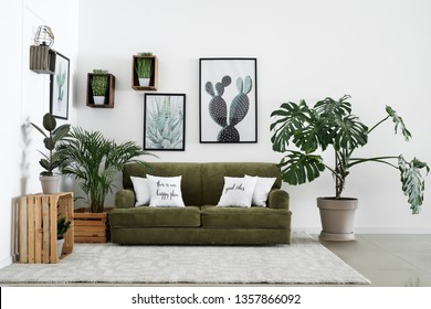 Interior of modern room with comfortable sofa and houseplants