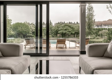 Interior in a modern style with columns, large windows and glass doors, tiled floor. There is a glass table with gray sofas. Outside there is a pool with deck chairs on the green trees background.