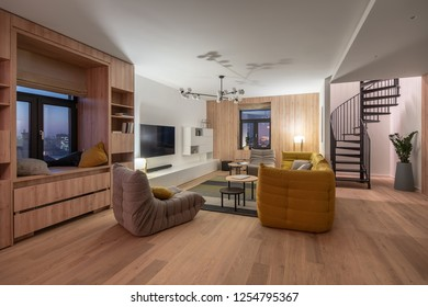 Interior in modern style with light walls and parquet with carpet. There is bookcase, windows, gray armchairs, yellow sofa, pillows, luminous lamps, TV, round tables, spiral staircase, green plants.