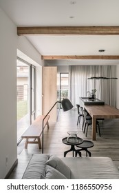 Interior in modern style with white walls, wooden beams on the ceiling, parquet. There is a table with chairs, kitchen island, sofa, metal stands, bench, floor lamp, large windows, fancy chandelier.