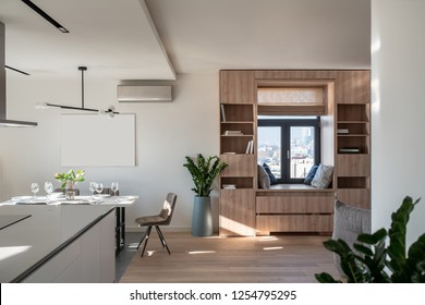 Interior in a modern style with white walls, parquet and tiles on the floor, kitchen zone. There is wooden bookcase, window with roman curtains, table with dishes, chairs, green plants, conditioner.