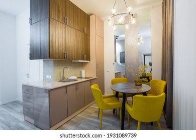 interior of a modern stylish kitchen in a small apartment, with furniture, in pastel colors, yellow with beige
