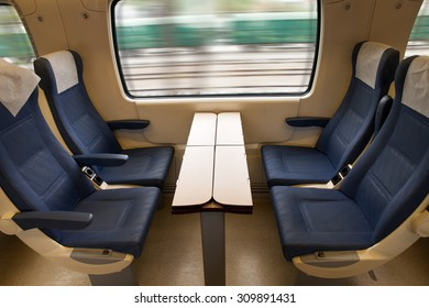 Interior of a modern train with comfortable seats and table, also power supply