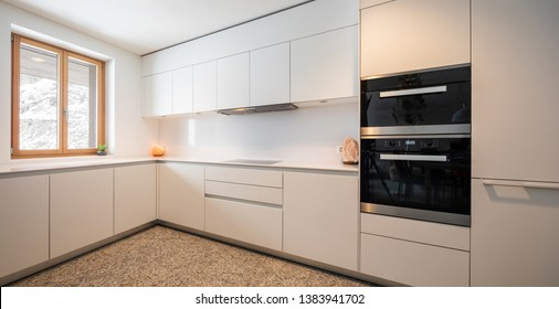 Interior of modern white kitchen with marble and mountain view. Nobody inside