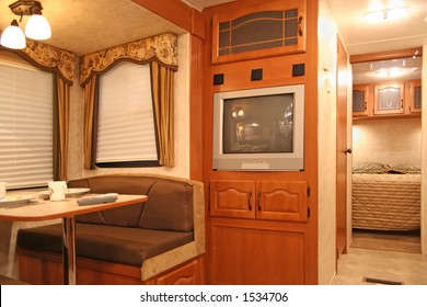 interior of motor home with dining table and dishes, tv, covered windows, and bedroom showing