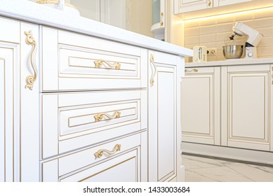 interior of neoclassical style white and gold wooden kitchen with island in luxury home