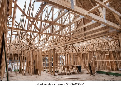 Interior of new home construction work site showing skeleton structure of walls and roof trusses constructed of wood 2x4's, newly installed windows, flooring built of waferboard, OSB, and plywood